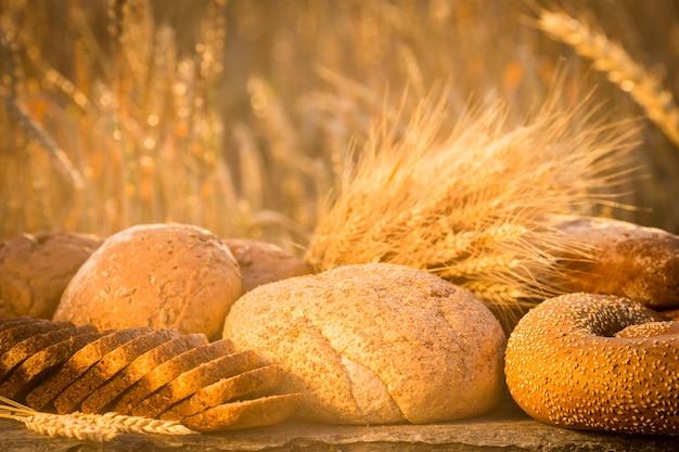 Brot und weizen auf dem holztisch im herbstfeld