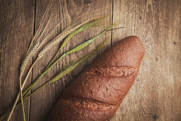 Brot und weizen auf einem holz. flach liegen.