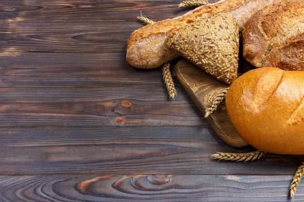 Brot und weizen auf hölzernem hintergrund. draufsicht mit kopienraum