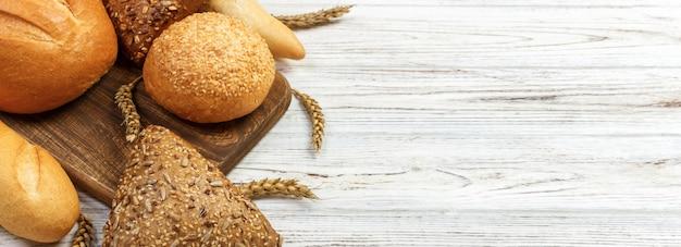 Brot und weizen auf weißem hölzernem.