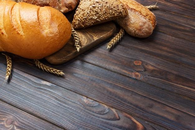 Brot und weizen auf weißem holz. ansicht von oben