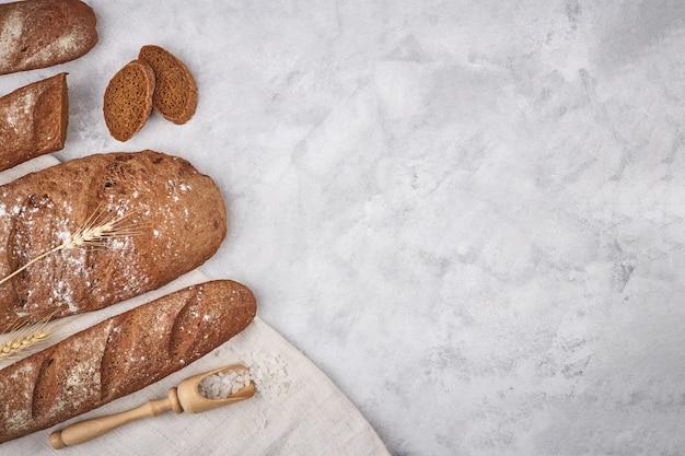 Brot verschiedener sorten auf einem holzhintergrund mit kopierraumhintergrund. konzept der bäckerei, kochen und lebensmittelgeschäft.