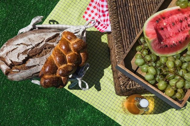 Brot; wassermelone; trauben und olivenöl flasche auf decke über rasen bei picknick