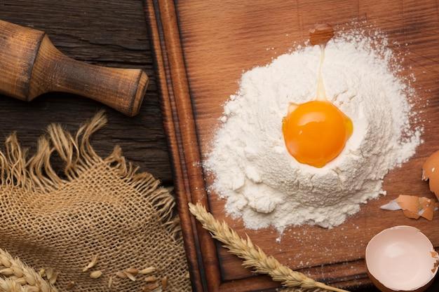 Brotback-backkonzept. eier, mehl, ährchen auf einem antiken holztisch.