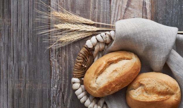 Brotbrötchen im korb auf rustikalem holz mit den weizenähren
