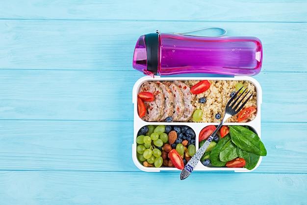 Brotdose hackbraten, bulgur, nüsse, tomaten und beeren. gesundes fitnessfutter. wegbringen. brotdose. ansicht von oben