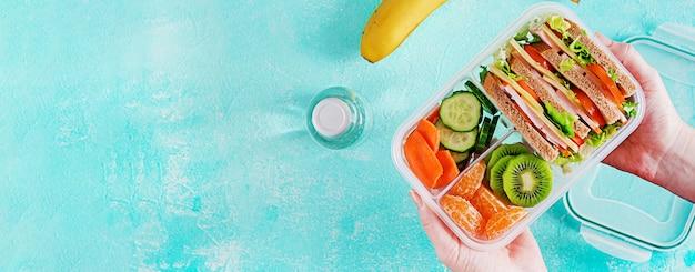 Brotdose in händen. schulbrotdose mit sandwich, gemüse, wasser und früchten auf tabelle. gesundes essgewohnheitskonzept. banner. ansicht von oben