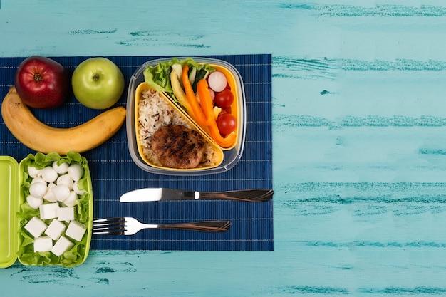Brotdose mit appetitlichen speisen und auf hellem holztisch