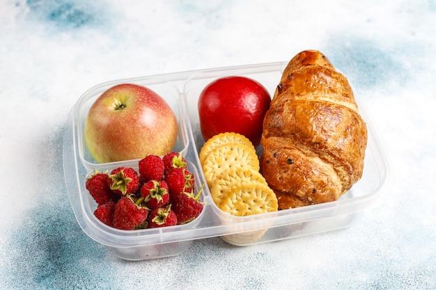 Brotdose mit frisch gebackenem croissant, crackern, früchten und himbeeren.