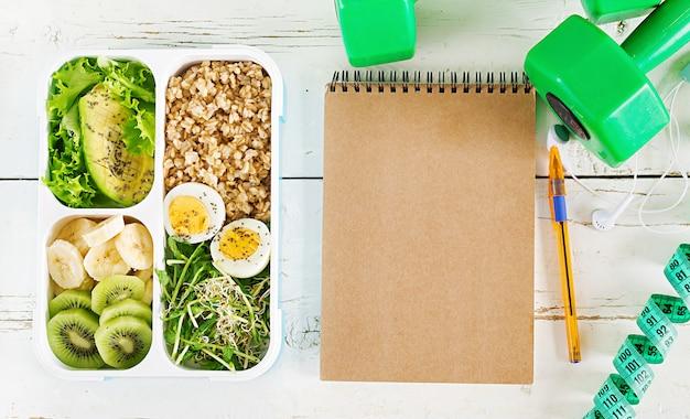 Brotdose mit gekochten eiern, haferflocken, avocado, mikrogrüns und früchten. gesundes fitnessfutter. wegbringen. brotdose. ansicht von oben