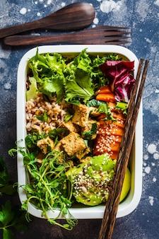 Brotdose mit gesundem veganen essen. bento box mit reis, süßkartoffel, tofu und gemüse.