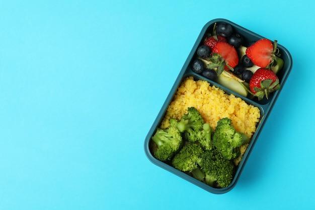 Brotdose mit leckerem essen auf blauem hintergrund