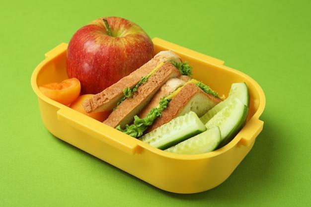 Brotdose mit leckerem essen auf grünem hintergrund