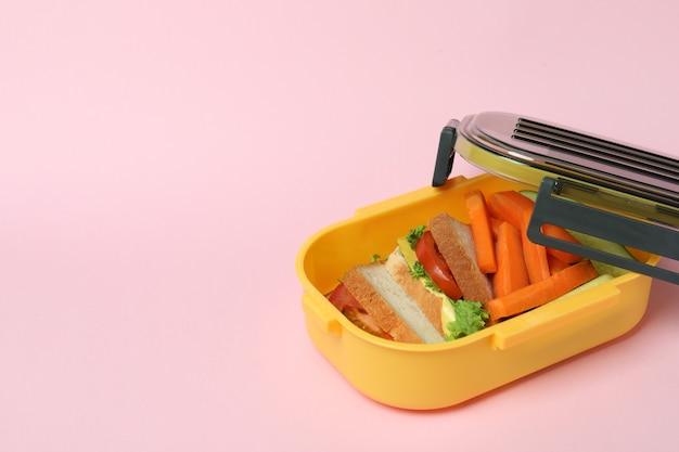 Brotdose mit leckerem essen auf rosa hintergrund
