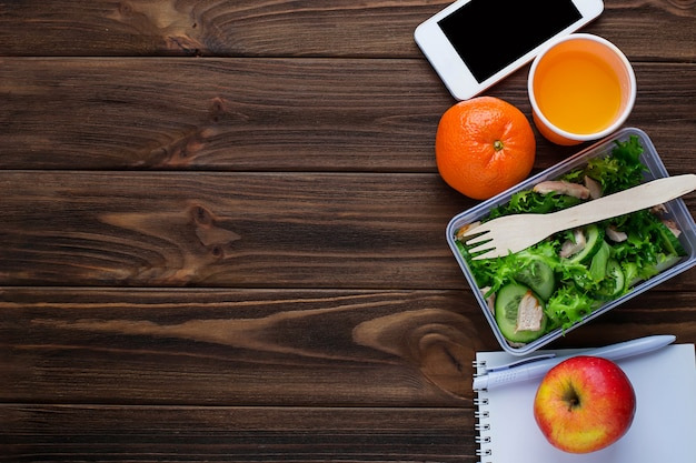 Brotdose mit salat, notizbuch und telefon
