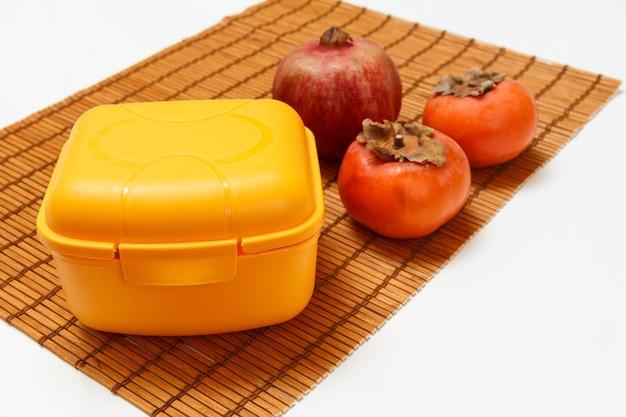 Brotdose, reifer granatapfel und kakifrüchte auf der bambusserviette. bio-früchte.