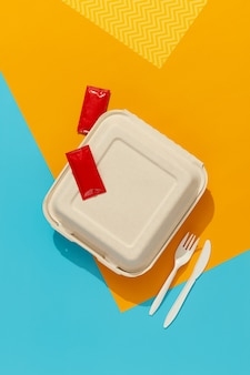 Brotdose und besteck auf buntem tisch. flat lay draufsicht food delivery konzept
