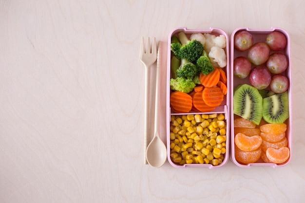 Brotdosen mit vegetarischem lebensmittel auf draufsicht des hölzernen hintergrundes. veganes mittagessen