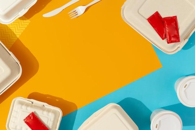 Brotdosen und besteck auf buntem tisch. flat lay draufsicht food delivery konzept