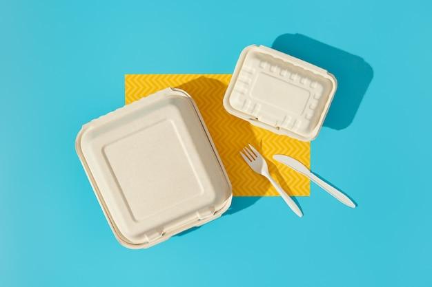 Brotdosen und besteck auf buntem tisch. flat-lay-food-lieferkonzept