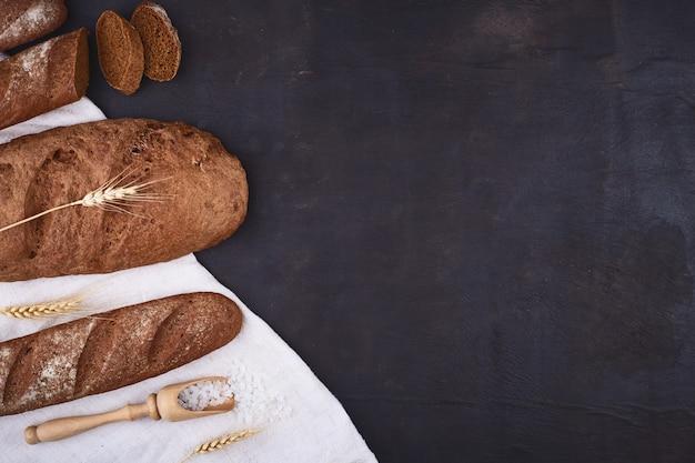 Brotgrenze auf holz mit kopierraumhintergrund. braune und weiße vollkornbrote stillleben zusammensetzung mit weizenohren verstreut. bäckerei und lebensmittelgeschäft konzept.