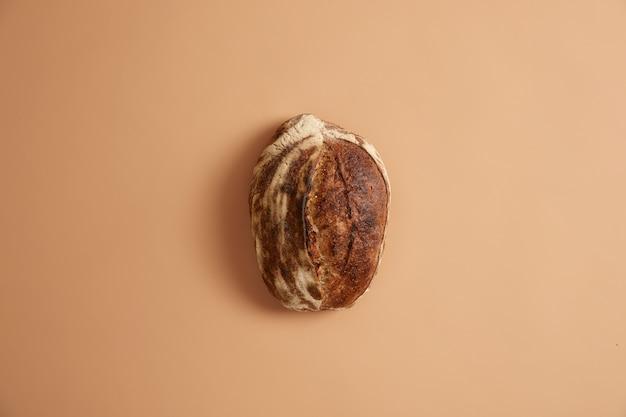 Brotlaib aus bio-zutaten vollkornweizen, buchweizen, roggen und ohne hefe. mehrkorn-backwaren auf beigem hintergrund. gesundes lebensmittel- und ernährungskonzept. jeden tag frische backen