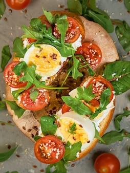 Brotsandwiche mit weichem hüttenkäse, rucola, eiern und kirschtomaten auf einem holzplatten-layout auf grauem hintergrund. ansicht von oben