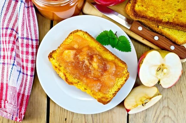 Brotscheibe mit apfelmarmelade und minze auf einem teller, apfelscheiben, ein glas marmelade, serviette, messer auf holzbrett im hintergrund