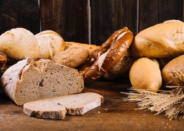 Brotscheibe und gebackenes vollkornbrot auf holztisch
