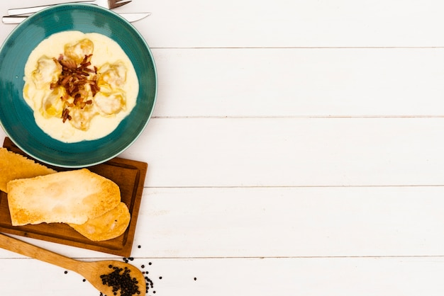Brotscheibe und sahnige ravioliteigwaren mit weißer soße auf holzoberfläche