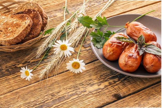 Brotscheiben auf holzbrett und gegrillte würstchen mit basilikum und petersilie auf dem teller. draufsicht mit holzbrettern im hintergrund..