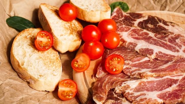 Brotscheiben, kirschtomaten, spinat und schinken. zutaten für ein sandwich oder bruschetta. gesundes kochen von frischen lebensmitteln