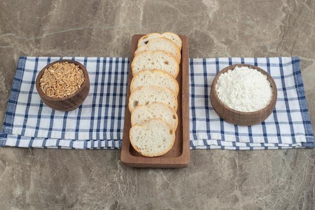 Brotscheiben, mehl und gerste auf tischdecke. hochwertiges foto