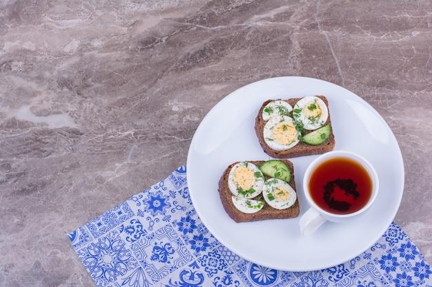 Brotscheiben mit ei und kräutern, serviert mit einer tasse tee