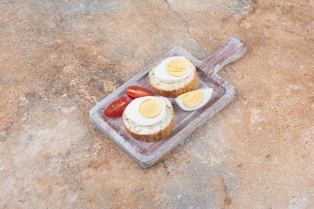 Brotscheiben mit gekochten eiern und tomatenscheiben auf holzbrett