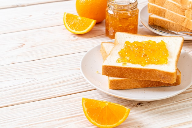 Brotscheiben mit orangenmarmelade und orangen