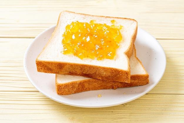 Brotscheiben mit orangenmarmelade zum frühstück