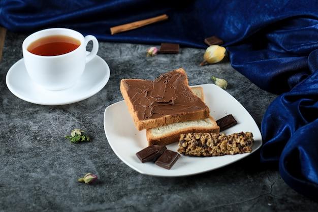 Brotscheiben mit schokoladencreme und einer tasse tee