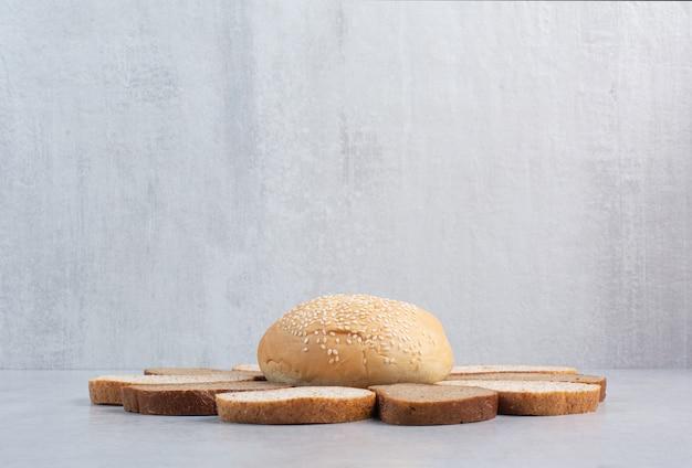 Brotscheiben und brötchen mit sesam auf blauem hintergrund. hochwertiges foto