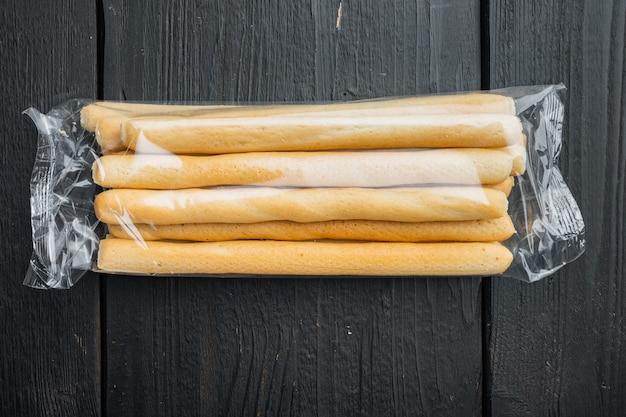Brotstangen mit olivenöl auf schwarzem holztisch, flach gelegt