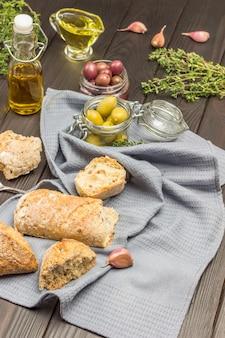 Brotstücke, knoblauchzehe und oliven im glas auf grauer serviette. olivenöl in der flasche, thymianzweige. draufsicht