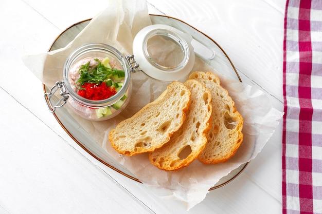 Brotstücke mit fischpastete auf weißem holztisch