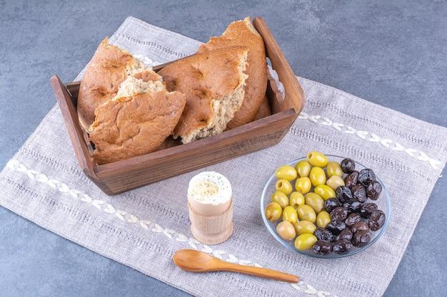 Brottablett, weich gekochtes ei und eine platte mit kernlosen oliven auf einer kleinen tischdecke auf marmoroberfläche