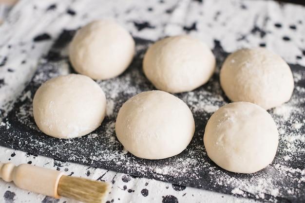 Brotteig auf schiefer mit mehl und pinsel