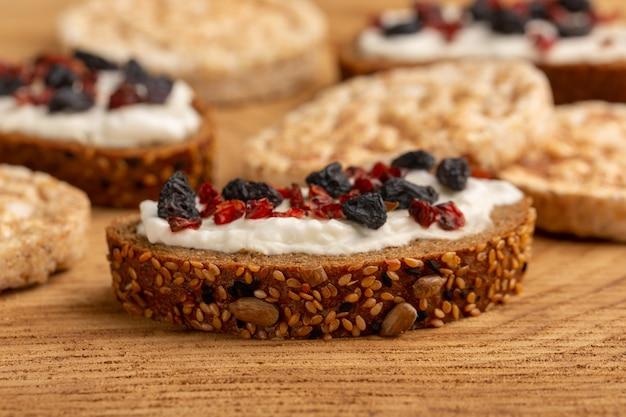 Brottoast aus der nähe mit sahne und getrockneten früchten auf holz