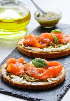 Brottoast mit gesalzenem lachs, pesto-sauce und frischkäse (ricotta)
