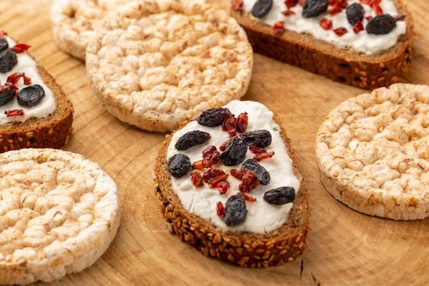 Brottoast mit getrockneten früchten und sahne sowie kekse auf holz