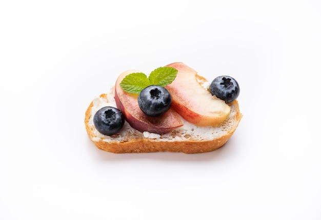 Brottoast mit pfirsich und blauer beere auf getrenntem weißem hintergrund