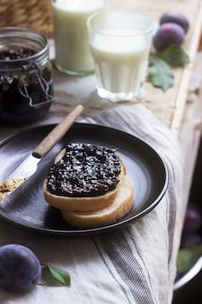 Brottoast mit pflaumenmarmelade, serviert mit milch und pflaumen. rustikaler stil.