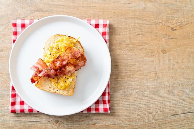 Brottoast mit rührei und speck auf weißem teller